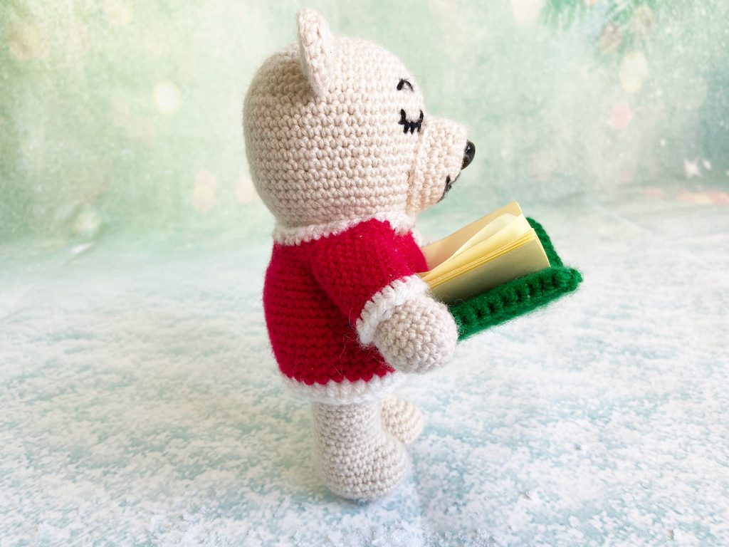 Singing Christmas bear crochet pattern holding book